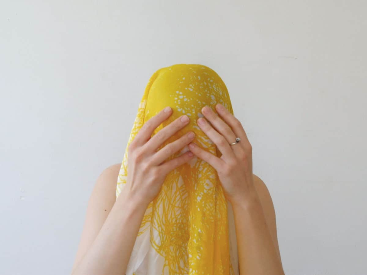 video still of person with head covered by a yellow and white scarf, hands to their face.