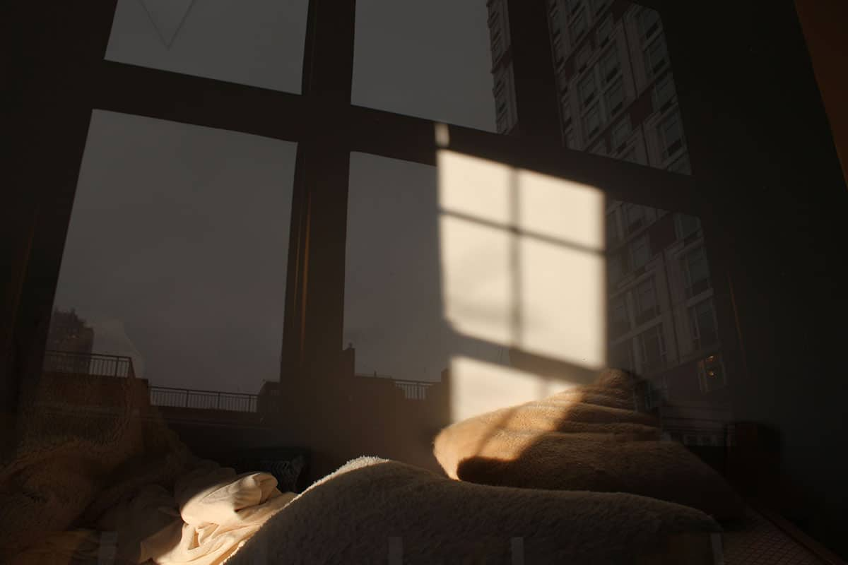 bed with sunlight overlaid with image of window.