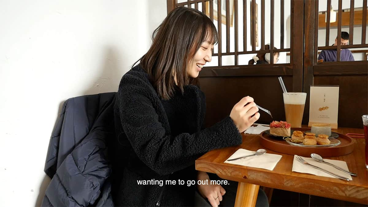 """still from video of woman sitting at a table and eating. the caption reads """"wanting me to go out more."""""""