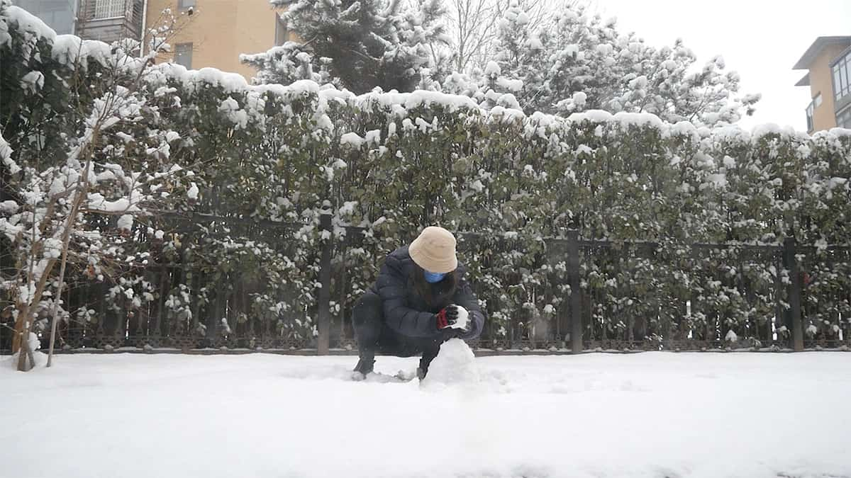 still from video of woman wearing a face mask in the snow making a small snowman.