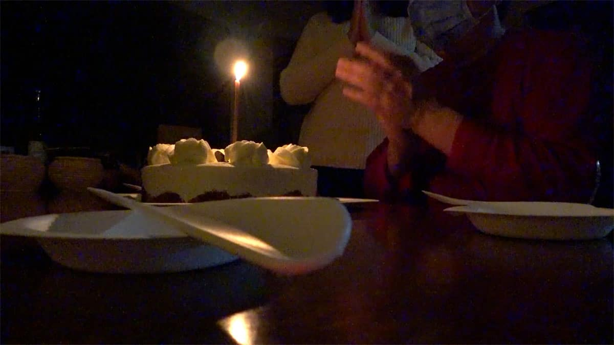 still from video of tabletop with birthday cake.