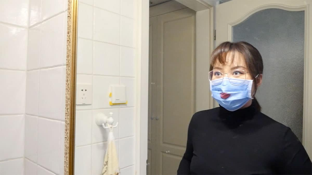 still from video of woman wearing a face mask looking in a mirror. there is lipstick on the face mask.