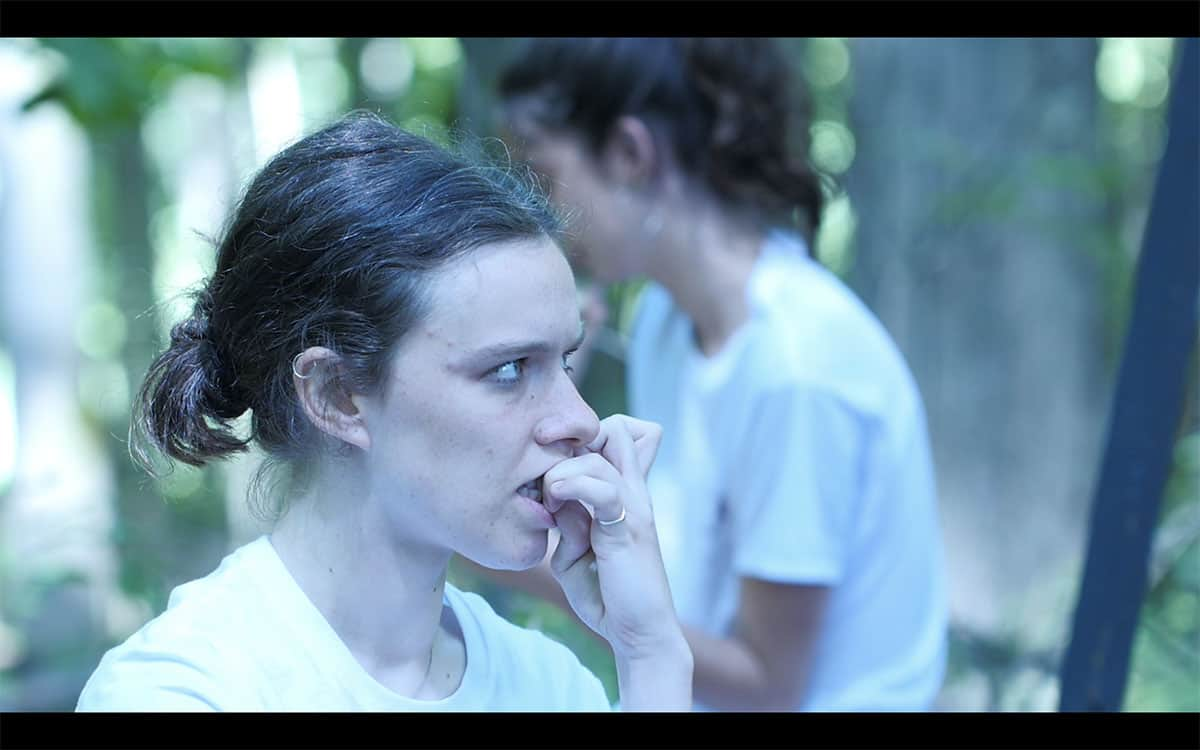 a video still of two people outside in white shirts, the person in the foreground with her hair tied back bites her fingernails. She has rings on her fingers and her upper ear