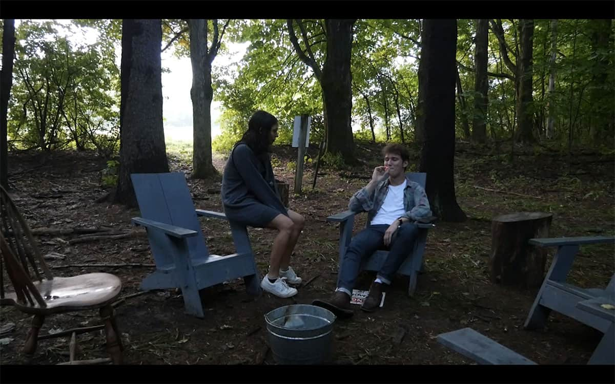 video still of two people sitting in a circle of wooden chairs around a metal bucket the woods, the person on the left has long hair and shorts and is perched on the arm of their chair looking at the person on the right wearing flannel and jeans and is smoking