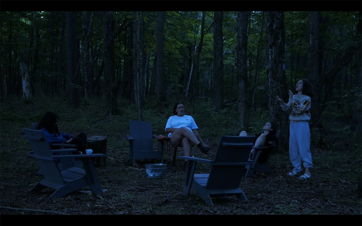 a video still of people in a ring of chairs around a metal bucket in the woods in dusky light all looking in different directions. One person is standing wearing a sweater and sweatpants and appears to be clapping while looking upwards