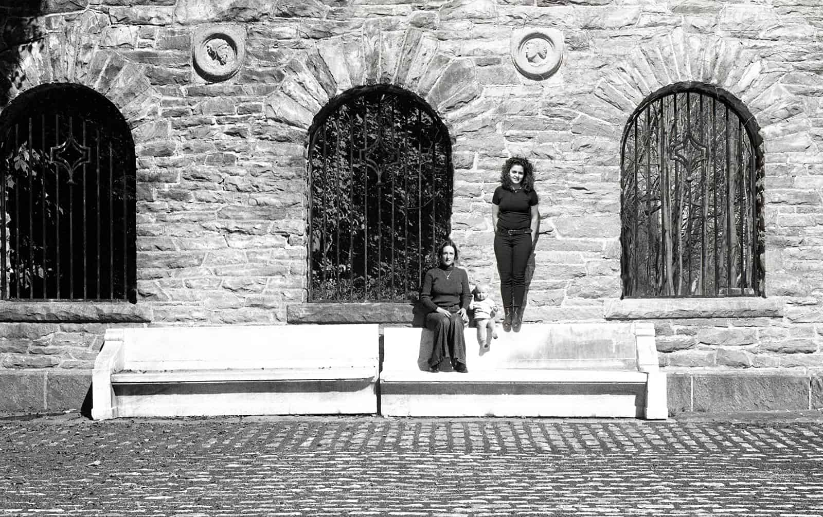 black and white photograph of two women and a baby in front of a brick wall.