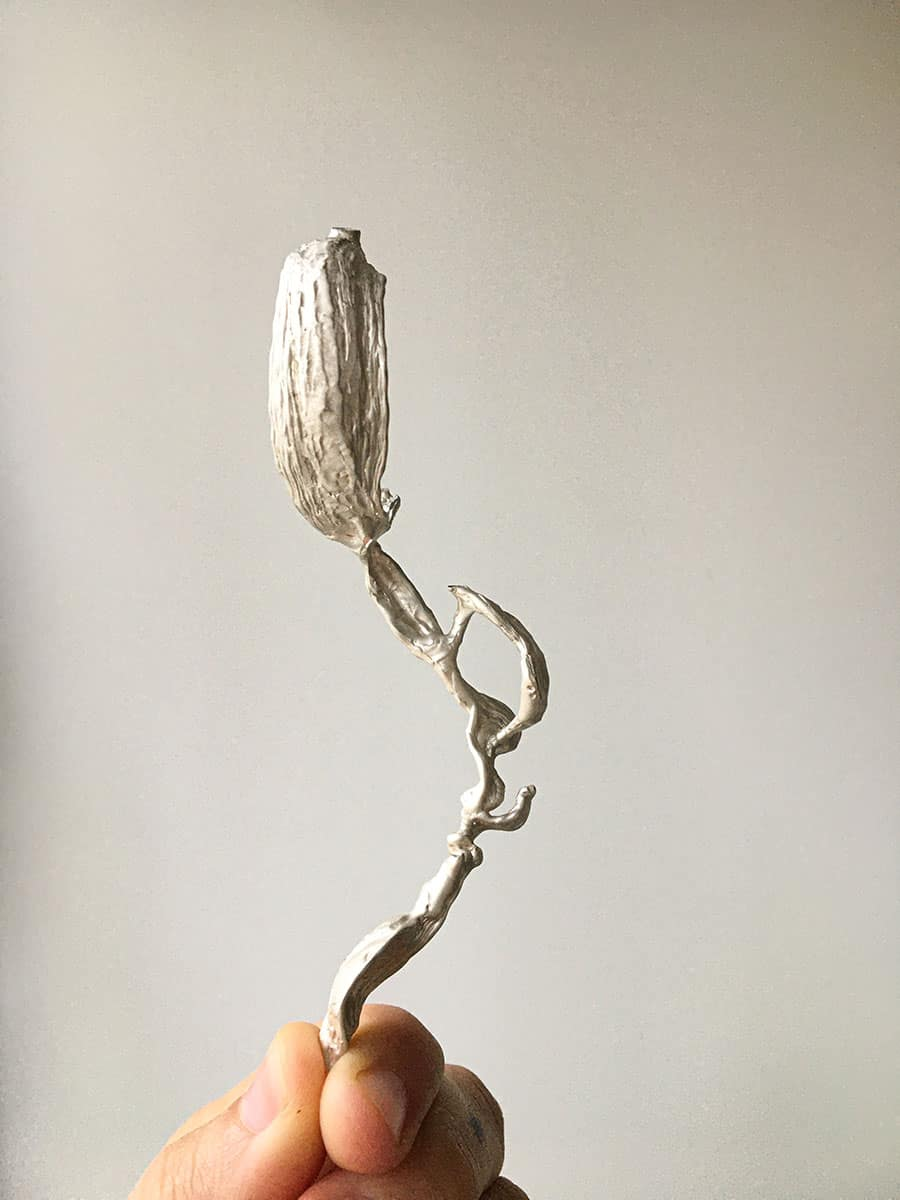 a hand holding an abstract shape made of cast silver