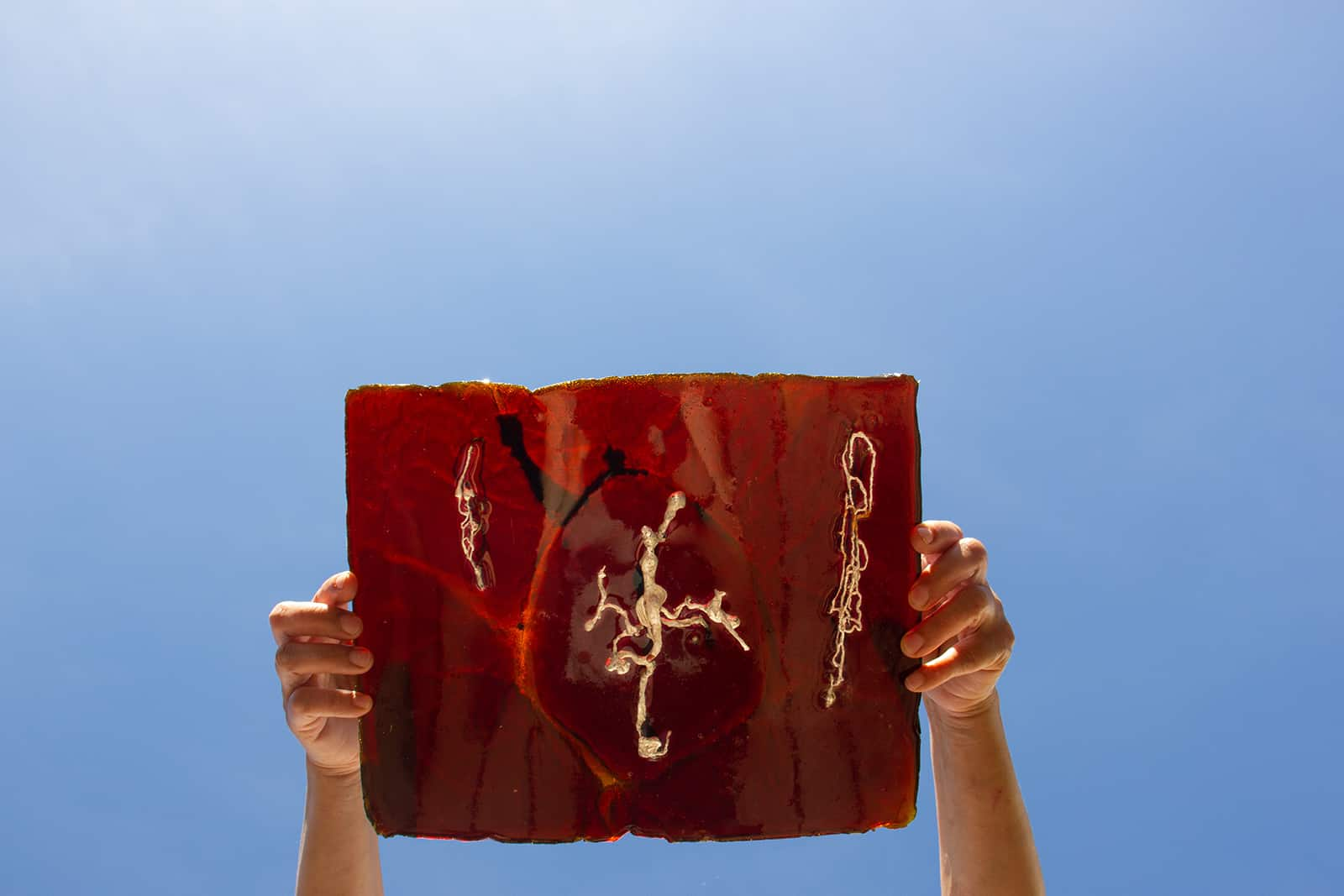 photograph of hands holding a piece of red-tinted resin with silver abstract shapes suspended in it.