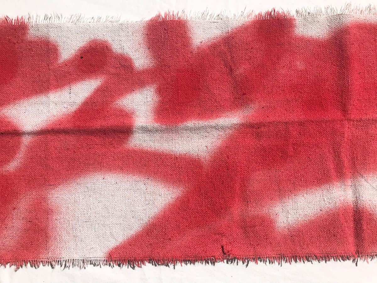 piece of canvas with red spray paint lines