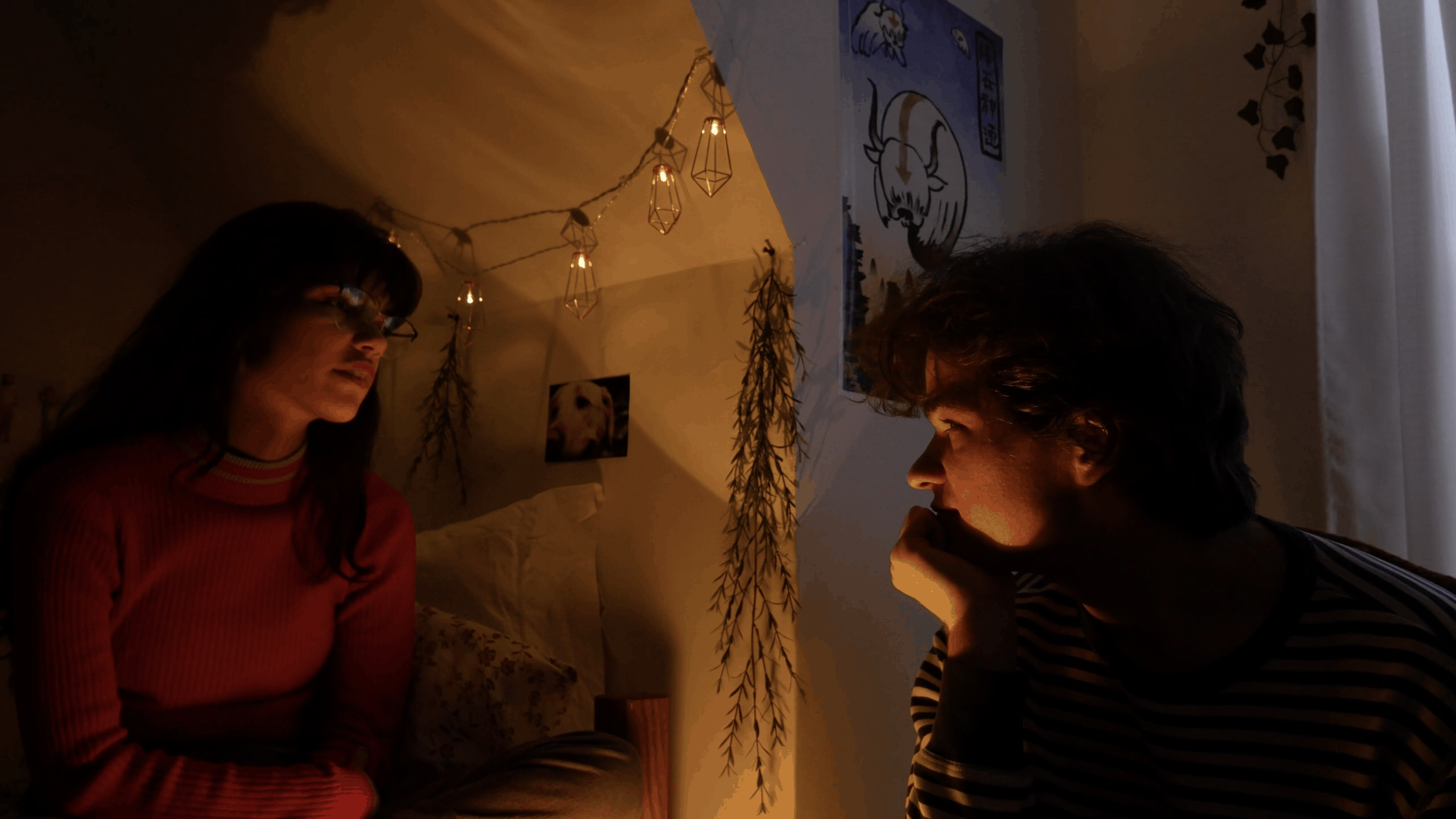 still image from video of two people facing each other in a white room lit with string lights
