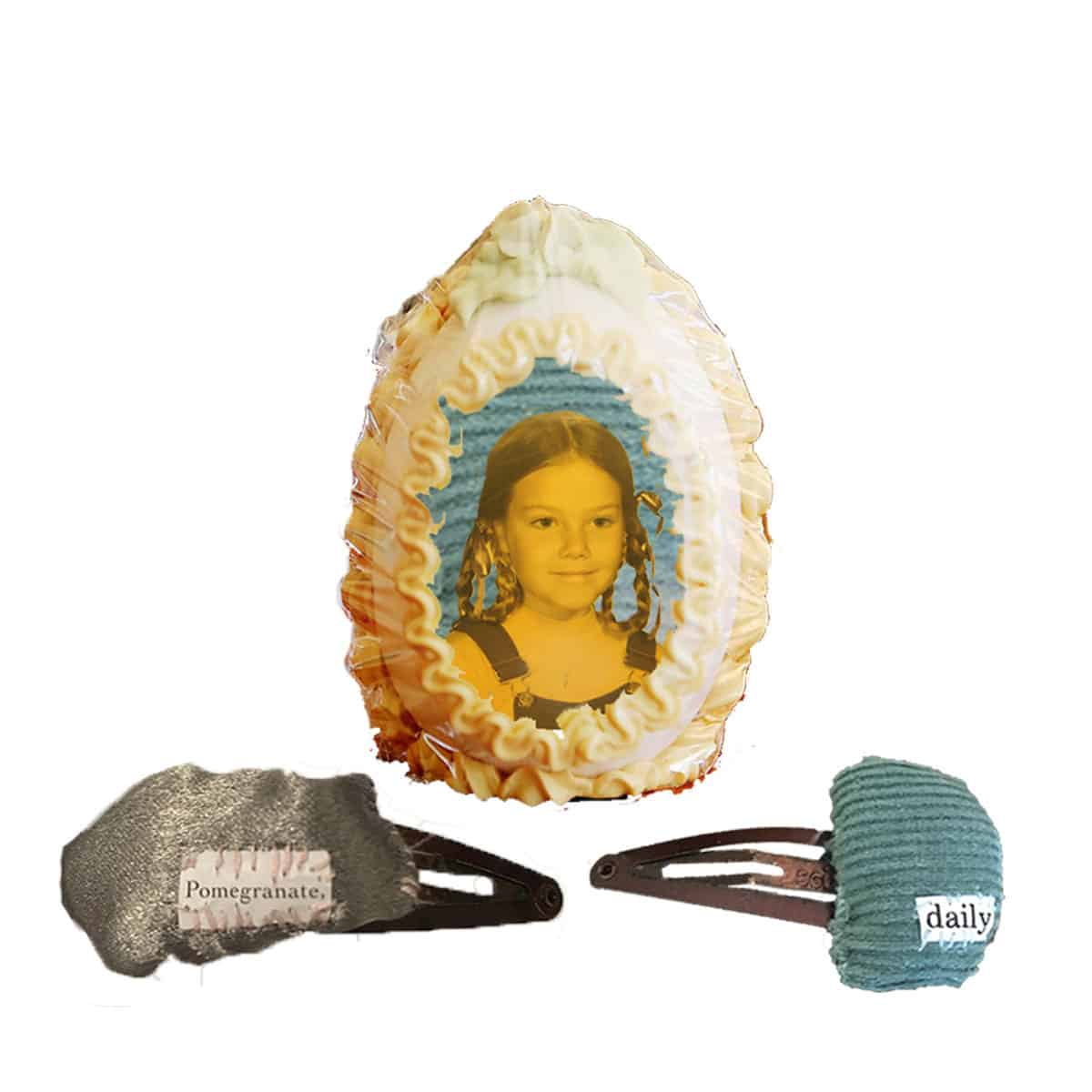 "digital collage of sugar easter egg with photograph of girl in the center, and two barrettes with the words ""pomegranate"" and ""daily""."
