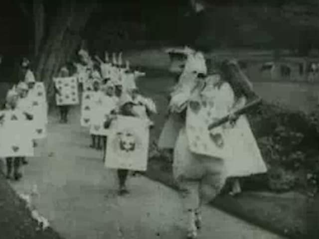 still from video of many people walking in two lines dressed as playing cards.