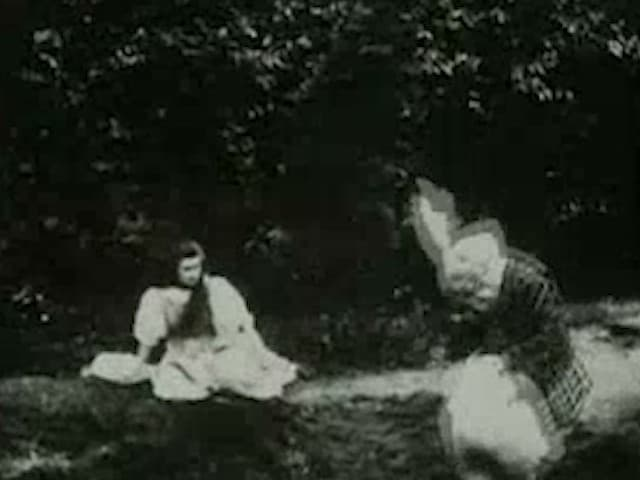 still from video of woman sitting on the ground and person dressed like white rabbit crouching