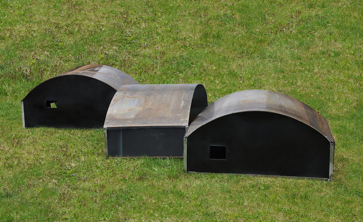 three arch-shaped metal, wood and rubber periscope sculptures