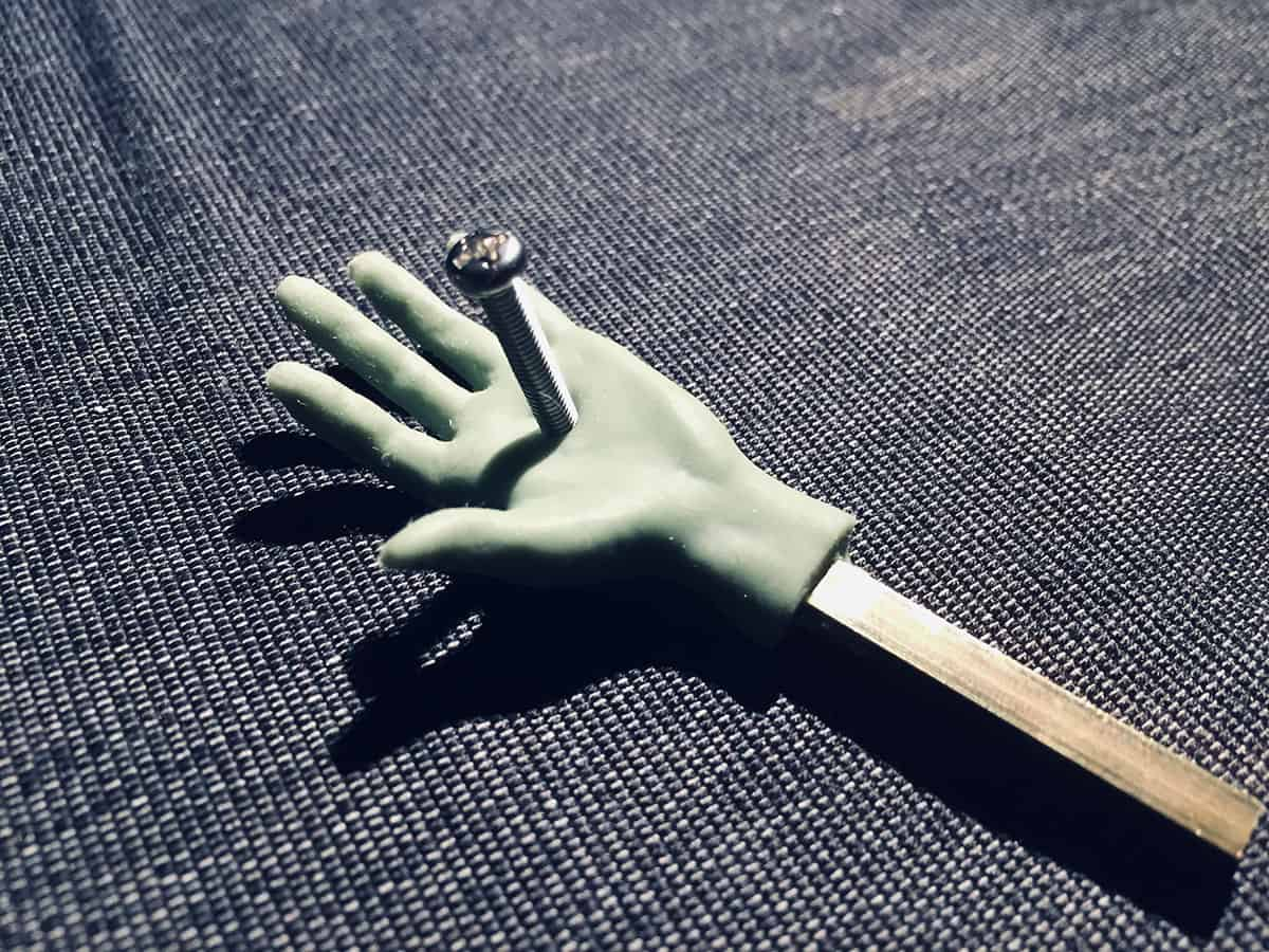 photograph of human looking pale green puppet hand nailed down to a patterned steely grey ground through the palm with a machine screw
