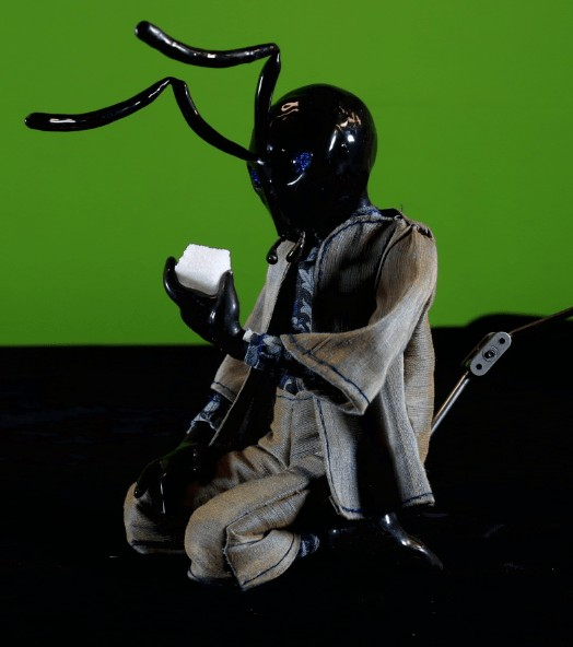 photograph of puppet with shiny black ant head looking at sugar cube on a green background