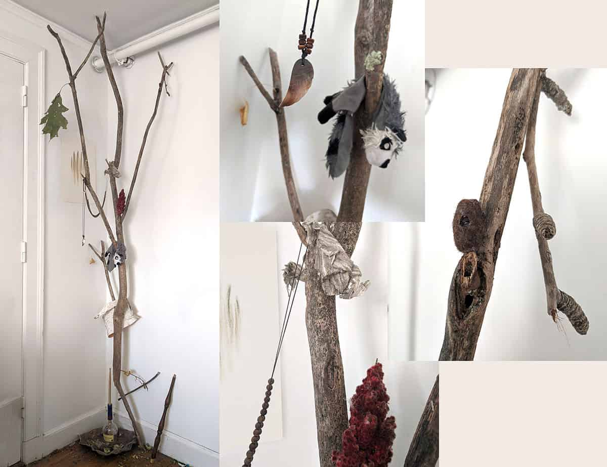 photograph of branch propped in the corner of a white room with a doorframe and pipe. Items are hanging on branch, including a dirty gray toy cloth animal and some natural materials