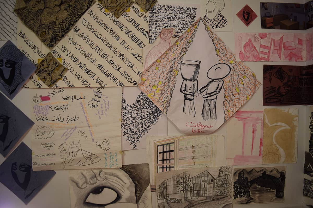 installation photo of many drawings hung on a wall. several drawings include arabic text.