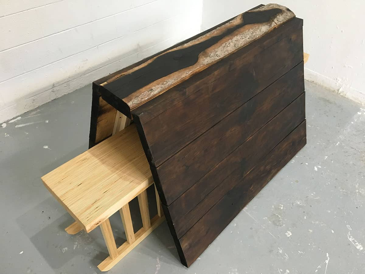 bench-like wood sculpture with 3-sided structure over